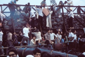 Desperate South Vietnamese climb aboard barges in the port of Saigon to escape advancing North Vietnamese troops on April 28, 1975, the day of the fall of Saigon. Photo ©Nik Wheeler/ Corbis.