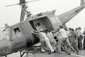 Crew members push a helicopter off a landing platform of the U.S.S. Kirk to clear room for more helicopters dropping off refugees. Photo courtesy Craig Compiano/USS Kirk Association.